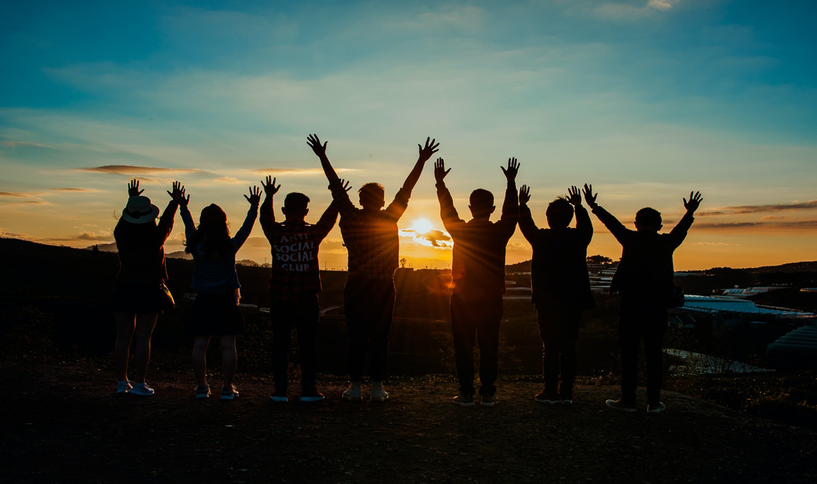 people watching sunset with raised hands