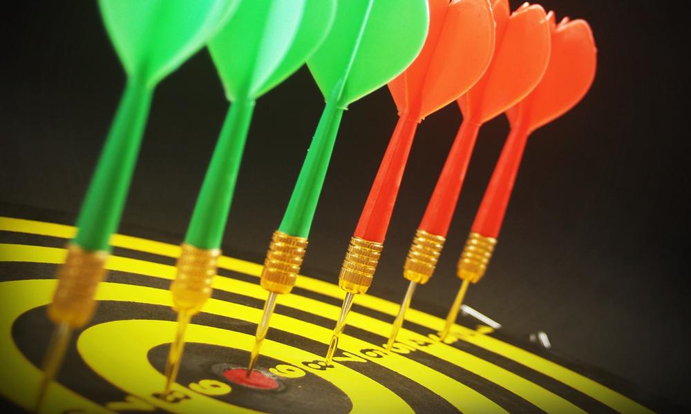 closeup of darts in a dartboard